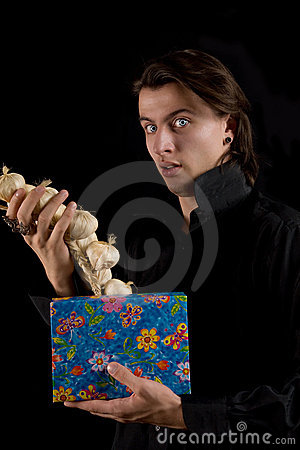 Funny vampire with gift box taking out garlic