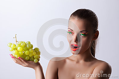 Funny woman with glow make-up and green grapes