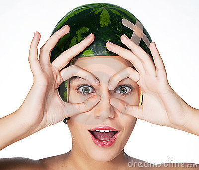 Funny young girl with watermelon as a helmet