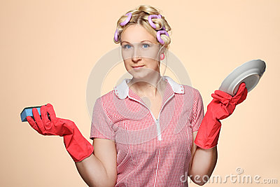 Funny young housewife with gloves holding scrubberr