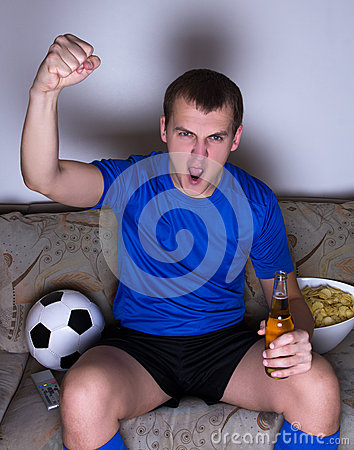 Funny young man watching football on tv and celebrating goal