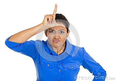 Funny young woman displaying loser sign on his forehead