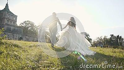Funzionamento delle coppie di nozze nel campo di erba vicino al castello sul tramonto stock footage