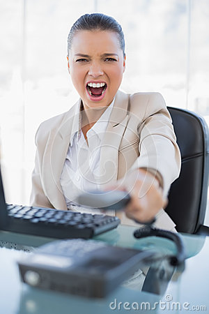 Furious businesswoman screaming while hanging up the phone