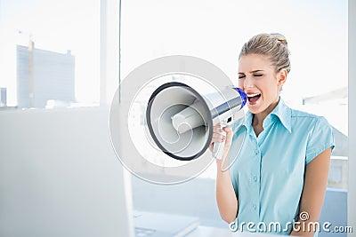 Furious elegant woman shouting in megaphone