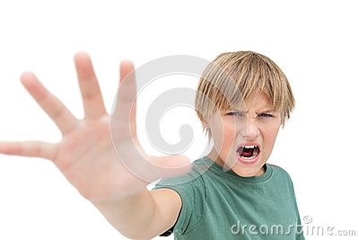 Furious little boy shouting and making stop sign with hand