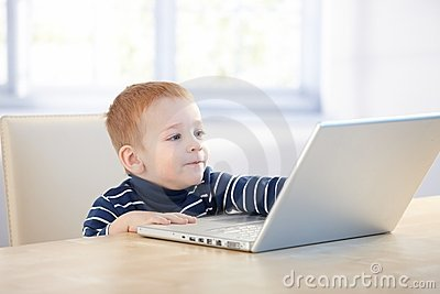 Future businessman using laptop at home