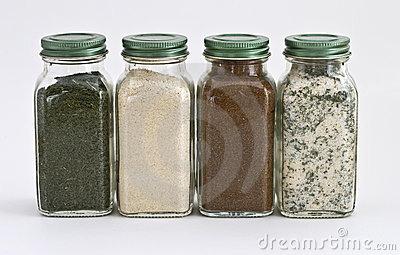 Fyra glass jars inställda kryddor