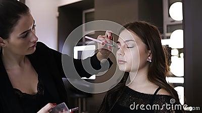 Gör den kvinnliga nake-upkonstnären för brunetten med röd manikyr sista handlag av ögonskuggor på ögonlocken av modellen brigham arkivfilmer