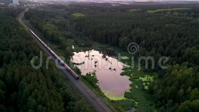 Güterzug mit Kohle- und Elektrolokomotive mit zweiseitiger Eisenbahn im Uralsumpiesee im Wald - Luftfotografie, stock video