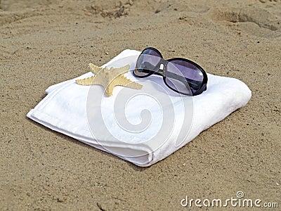 Gafas de sol y estrellas de mar en la toalla blanca