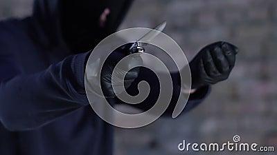Gagster w maski i kapiszonu grożeniu z nożowym wymagającym pieniądze, niebezpieczeństwo zdjęcie wideo