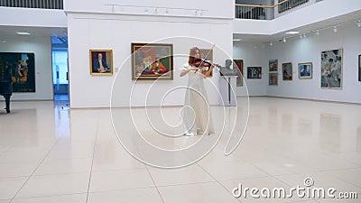 Galerijhal met een vrouwenhater die het instrument speelt stock video