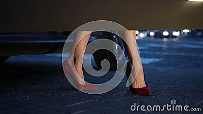 Gambe del ` s della donna in talloni che fanno un passo dall'automobile alla notte video d archivio