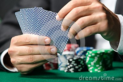 Gambler playing poker cards with chips on the poker table