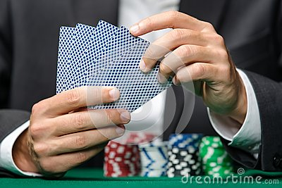 Gambler playing poker cards with poker chips on the table