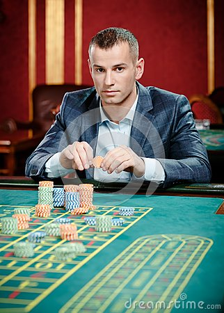 Gambler playing roulette at the casino table