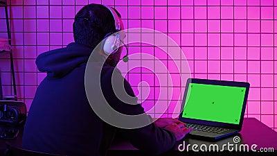 Gamer professionnel jouant le jeu vid?o sur son ordinateur portable. Affichage vert de maquette d'?cran banque de vidéos