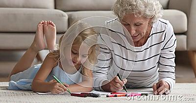 Gamla farmor lär ut små barnbarn som ritar med kängpenna tillsammans lager videofilmer
