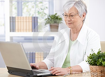 Gammal lady som använder bärbar dator