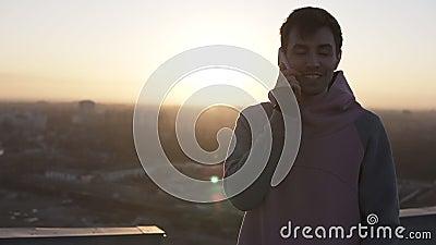 Garçon de brune dans la position occasionnelle sur le toit dans des fusées de lentille et appeler utilisant son smartphone Parler banque de vidéos
