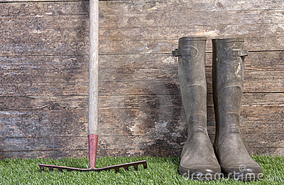 Garden boots and rake on grass