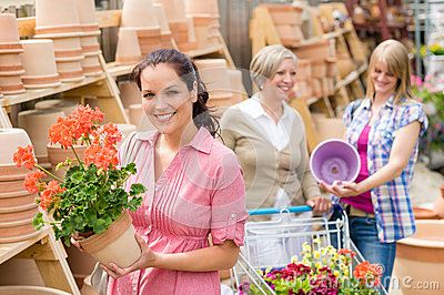 Garden centre woman hold red potted geranium