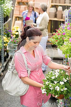 Garden centre woman hold white surfinia flower