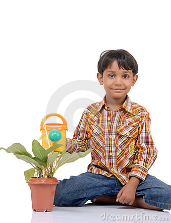 Gardener little boy watering plant