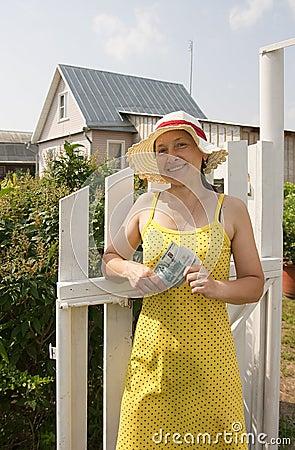 Gardener  outdoor in her garden with cash