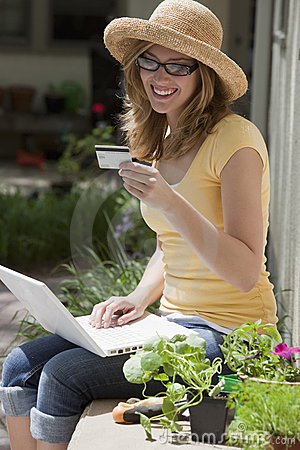 Gardener sitting outside using credit card and lap