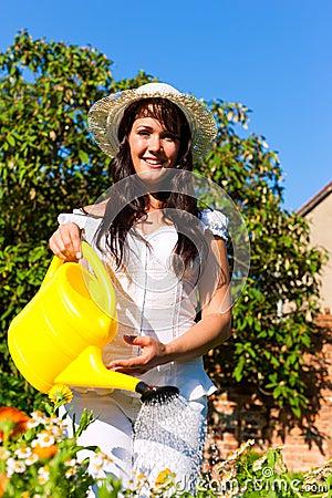 Gardening in summer - woman watering flowers