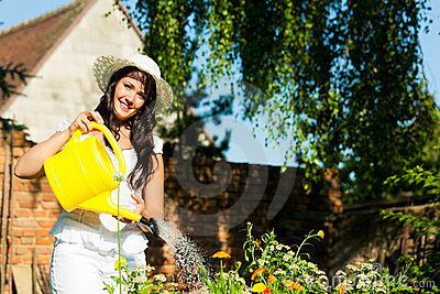 Gardening in summer - woman watering flowers