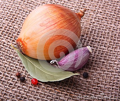 Garlic clove, onion on burlap background