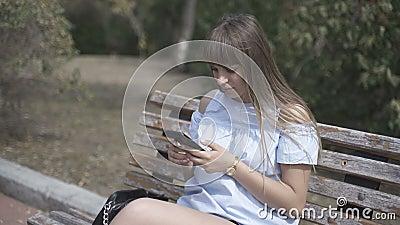 Garota com um telefone sentado no banco vídeos de arquivo