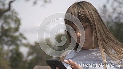 Garota com um telefone sentado no banco video estoque