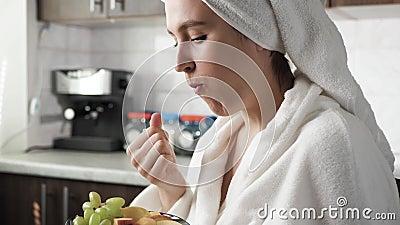 Garota come fruta Mulher na cozinha em roupão branco com toalha na cabeça come fruta Alimentação adequada, vegetarianismo vídeos de arquivo