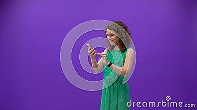 A garota curly joga em um iPhone 11pro em uma mão sobre um fundo roxo vídeos de arquivo