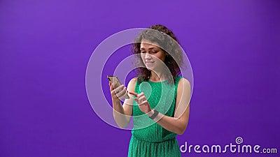 A garota curly joga em um iPhone 11pro em uma mão sobre um fundo roxo filme
