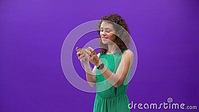 A garota curly joga num novo iPhone em uma mão sobre um fundo roxo filme