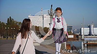 Garota da escola está caminhando no trem do mar com a mãe, Steadicam, vista da frente vídeos de arquivo
