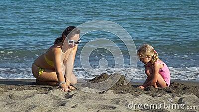 Garota Pequena com o Castelo da Areia da Mãe vídeos de arquivo
