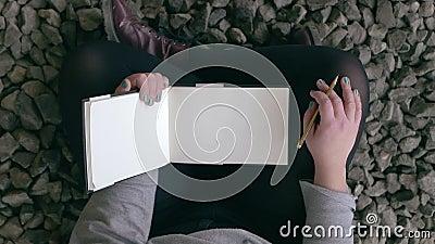 Garota segura seu esboço e lápis para se preparar para desenhar Sentado em pedras pequenas filme
