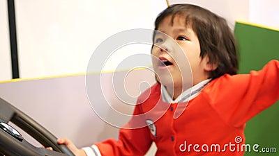 A garotinha asiática gostou de dirigir um jogo de carro de arcade, e convidou seus pais para se sentarem ao lado dela filme