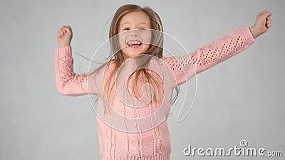 Garotinha bonitinha, parada, pulando levantando a mão, se divertindo isolada em um estúdio branco vídeos de arquivo