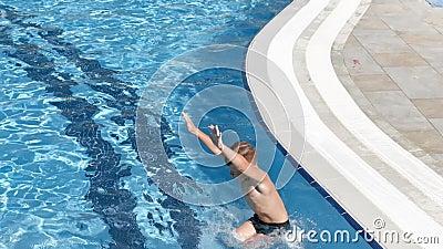 Garoto curtido ativo pulando na piscina cercado por água salgada em câmera lenta filme