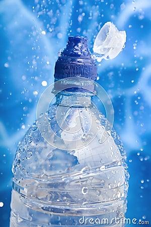 Garrafa de água do close up em um respingo da água