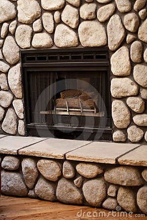 Gas fireplace with big rocks on wall