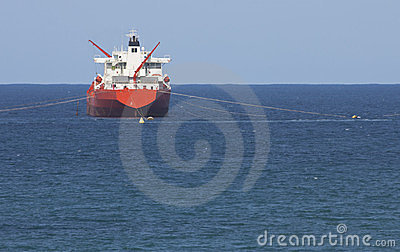 Gas tanker on ocean with blue sky