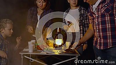 Gastfamilien essen Grillbratwurst beim Abendessen in Waldwanderung auf dem Campingplatz Mama, Papa, Sohn und Tochter frittieren stock footage